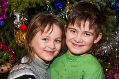 Irmão e irmã perto de uma árvore de Natal Fotografia de Stock Royalty Free