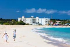 Dois miúdos que andam ao longo de uma praia nas Caraíbas Fotografia de Stock Royalty Free