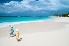 Dois miúdos que andam ao longo de uma praia nas Caraíbas imagem de stock royalty free