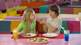 Irmão e irmã que apreciam a pizza do chocolate no restaurante das crianças video estoque