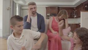 Irmão e irmã que discutem no primeiro plano, na mãe confusa e no pai sentando-se no sofá no fundo navega??o filme
