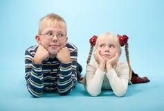 Irmão e irmã que encontram-se para baixo no assoalho fotografia de stock royalty free