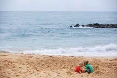 Irmão e irmã que jogam com areia e água em uma praia tropical, vestida no roupa de mergulho protetor imagens de stock