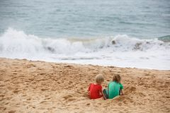 Irmão e irmã que jogam com areia e água em uma praia tropical, vestida no roupa de mergulho protetor fotos de stock