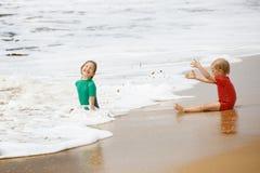 Irmão e irmã que jogam com areia e água em uma praia tropical, vestida no roupa de mergulho protetor foto de stock