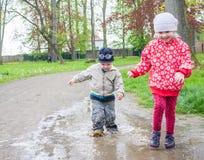 Irmão e irmã que jogam em uma poça Fotografia de Stock