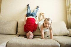 Irmão e irmã que jogam no sofá: o menino está de cabeça para baixo fotografia de stock