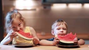 Irmão e irmã que sentam-se na tabela na cozinha Menino e menina que comem a melancia suculenta, olhando à câmera