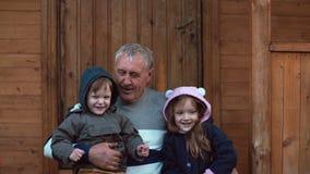 Irmão e irmã que sentam-se nos joelhos do avô s O ancião abraça seus neto e neta 4K fotos de stock royalty free