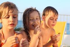 Irmão e irmãs na praia que comem o gelado Fotografia de Stock Royalty Free