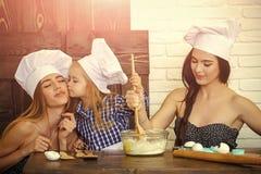 Irmão e irmãs nos chapéus do cozinheiro chefe que preparam a massa imagens de stock royalty free