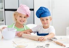 Irmão feliz e irmã que preparam uma massa de pão Imagens de Stock