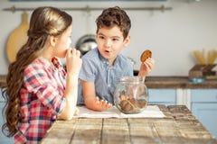 Irmão feliz que come cookies com sua irmã fotos de stock royalty free