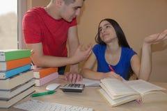 Irmão mais idoso que ajuda escrevendo a lição seu estudante da irmã que olha se Fotografia de Stock Royalty Free