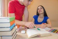 Irmão mais idoso que ajuda a irmã nova com lição da escrita Foto de Stock