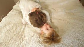 Irmão mais novo e irmã que abraçam na cama Menino e menina felizes da família Handheld filme