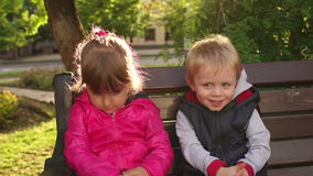 Irmão mais novo que abraça sua irmã triste no parque vídeos de arquivo