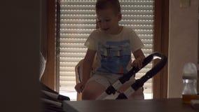 Irmão mais velho que tranquiliza a irmã júnior para dormir no transporte de bebê video estoque