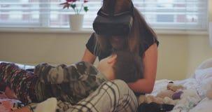 Irmão pequeno dos momentos muito bonitos que joga com sua irmã do adolescente na cama, ao mesmo tempo ela que usa um VR video estoque