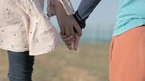 Irmão pequeno e irmã do close-up da mão que guardam as mãos que estão entre a área do deserto do campo de refugiados filme