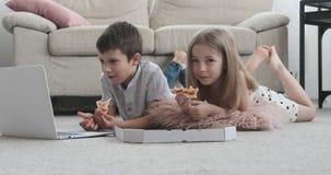Irmão que come a pizza e que olha o filme video estoque