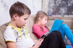 Irmão que senta-se com a tabuleta eletrônica nas mãos, irmã que lê um livro no sofá na sala foto de stock