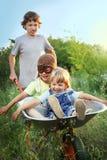 Irmão três que joga no plano usando carros de jardim Imagens de Stock