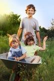 Irmão três que joga no plano usando carros de jardim Fotografia de Stock