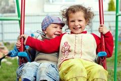 Irmãos aciganados pequenos sujos mas felizes em balanços Foto de Stock