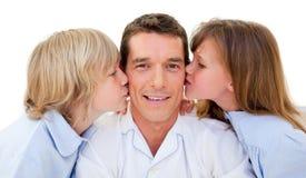 Irmãos adoráveis que beijam seu pai imagens de stock royalty free