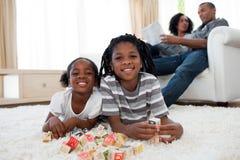 Irmãos africanos que jogam cubos alfabéticos Fotos de Stock