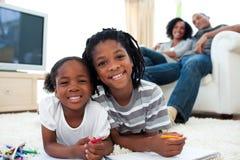 Irmãos alegres que jogam o encontro no assoalho Foto de Stock Royalty Free
