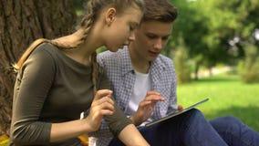 Irmãos amigáveis que enrolam páginas na tabuleta, em redes sociais e em jogos onlines filme