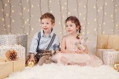 Irmãos caucasianos dos amigos das crianças que comemoram o Natal ou o ano novo Imagens de Stock Royalty Free