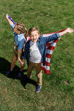 Irmãos com a bandeira americana que tem o divertimento fora, comemorando o 4 de julho - Dia da Independência Imagem de Stock Royalty Free