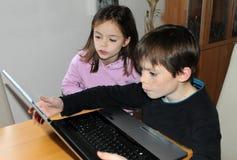 Irmãos com computador imagens de stock