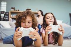 Irmãos com os controladores que jogam o jogo de vídeo no tapete em casa imagens de stock