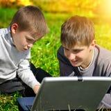 Irmãos com portátil Imagem de Stock