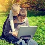 Irmãos com portátil Foto de Stock