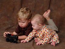 Irmãos com trem do brinquedo Fotografia de Stock Royalty Free