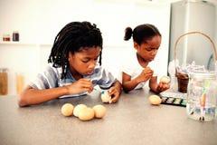 Irmãos concentrados que pintam ovos ilustração stock