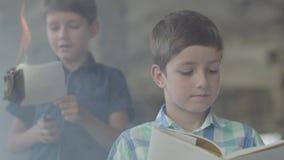 Irmãos de gêmeos pequenos bonitos na sala fumarento Um menino iluminou o papel com um isqueiro e uma outra leitura da criança no filme