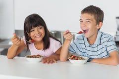 Irmãos de sorriso que comem o cereal para o café da manhã na cozinha Fotos de Stock Royalty Free