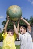 Irmãos e globo Foto de Stock Royalty Free