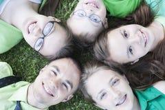 Irmãos e irmãs que encontram-se na grama Imagens de Stock