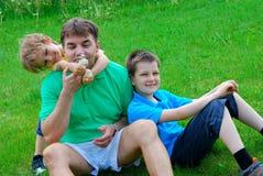 Irmãos e tio no prado Imagens de Stock