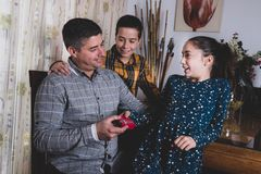 Irmãos felizes que dão o presente para genar no dia de pai foto de stock