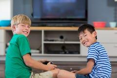 Irmãos felizes que jogam jogos de vídeo na sala de visitas imagens de stock