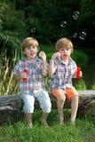 Irmãos gêmeos pequenos que sentam-se no banco de madeira e em bolhas de sabão de sopro no parque do verão Fotos de Stock Royalty Free