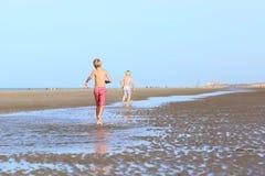 Irmãos gêmeos que correm na praia foto de stock